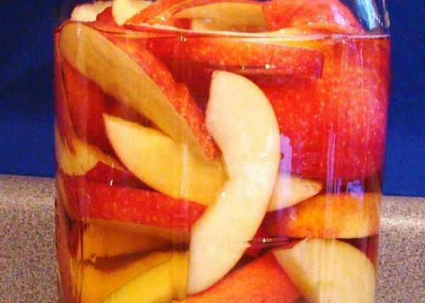 Umpleți conservele cu mere și turnați alcool